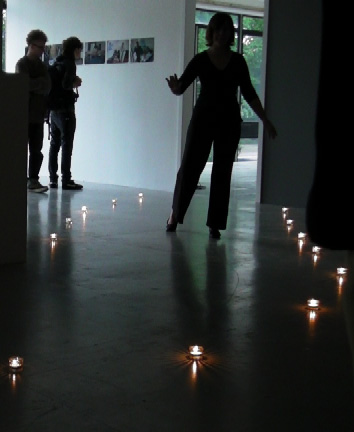 The silhouette of a woman in a gallery walking a candlelit pathway