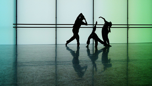 Three dancers silhouetted against a green background
