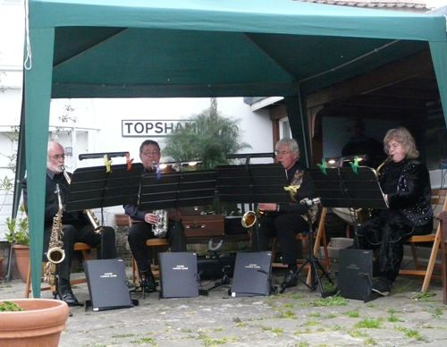 4 saxophone players under a gazebo