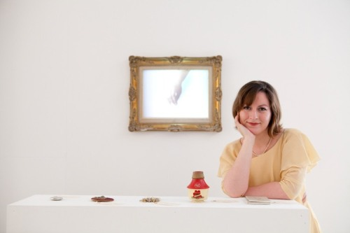 A woman surrounded by objects and a framed picture