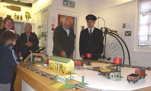 A man dressed as a train conductor demonstrating a model railway
