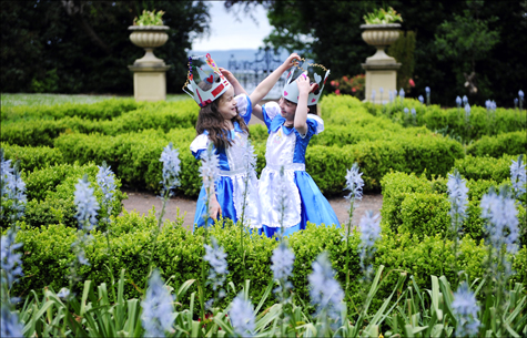 Two girls dressed as Alice in Wonderland playing in a formal garden