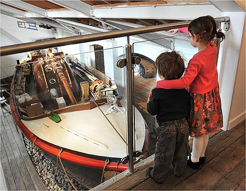 Two children looking at a historic boat in a museum