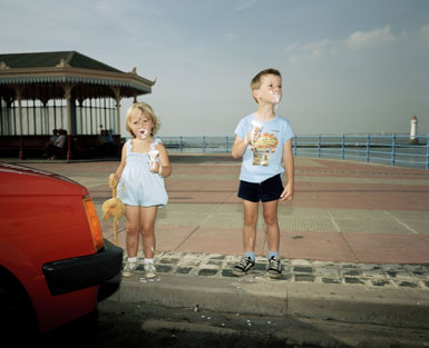 a photo of two children eating melting icecreams by the seaside