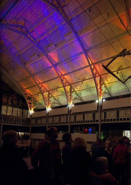 Visitors admiring sparkling lights on a curving ceiling in a historic building