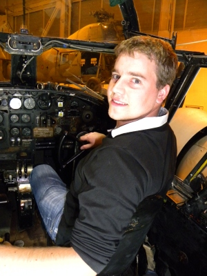 A young man sitting in an aeroplane cockpit