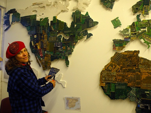 A woman in a red hat making a world map installation out of circuit boards