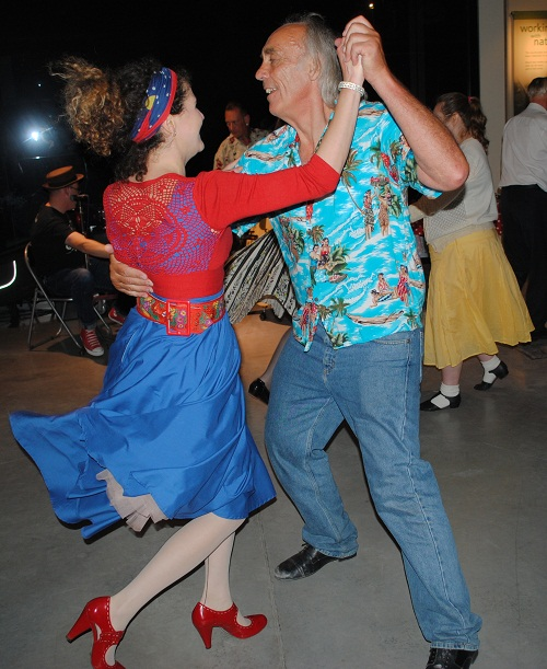 A colourfully dressed couple swing dancing in a museum
