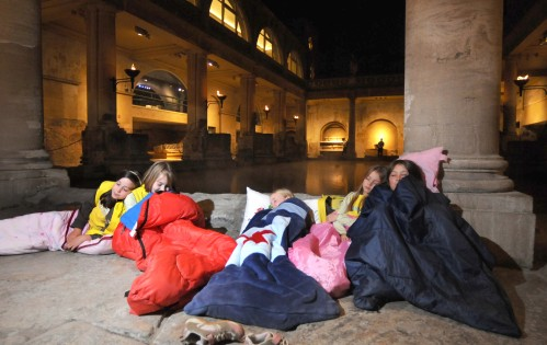 A group of girls in sleeping bags next to a Roman bath at night
