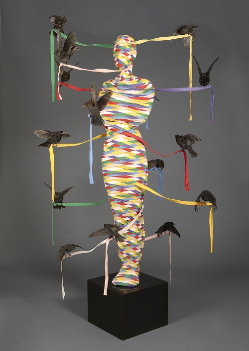 A maypole shaped like a human surrounded by taxidermy birds