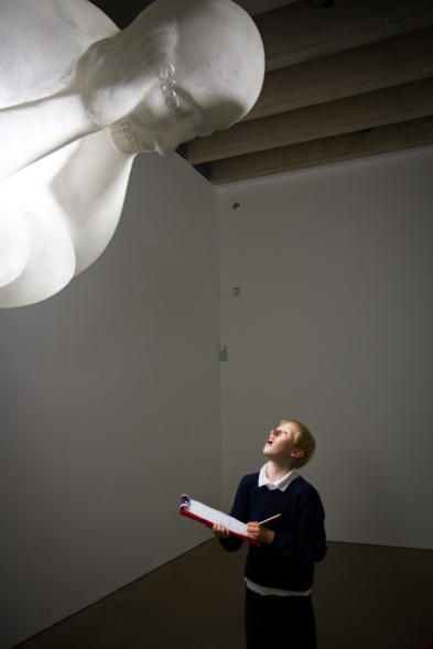 A child looking upwards at a large glowing white sculpture