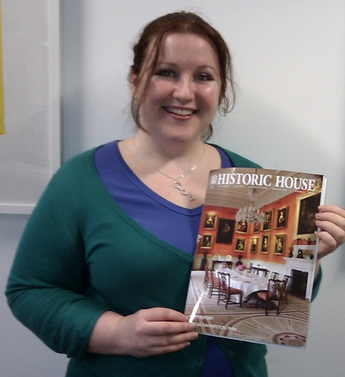 A woman smiling holding a copy of Historic House Magazine