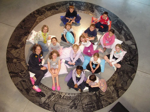 A group of children sitting in a museum rotunda with bedding