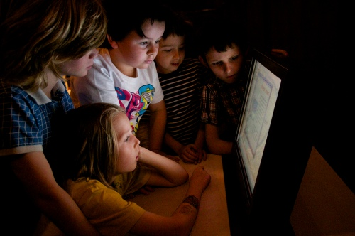 A group of children looking at a computer