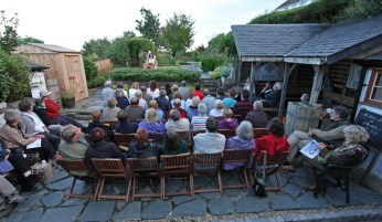 A view of the backs of the audience sitting on chairs in a garden courtyard