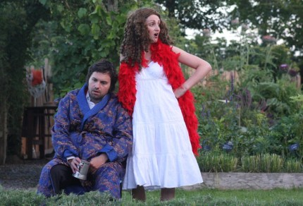 A man and a woman in a red feather boa performing in a garden