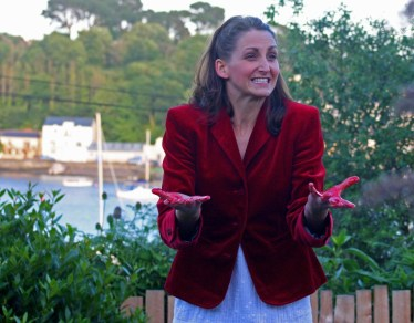 A woman in a red jacket with blood on her hands