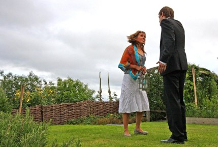 A man and a woman perform in a garden