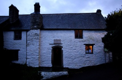 A ancient white cottage at dusk