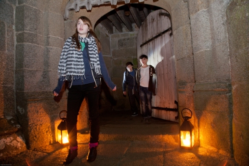 Three children in dark corridor of castle