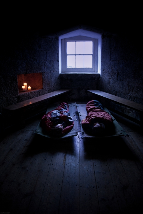 Two children in sleeping bags on camp beds in a castle