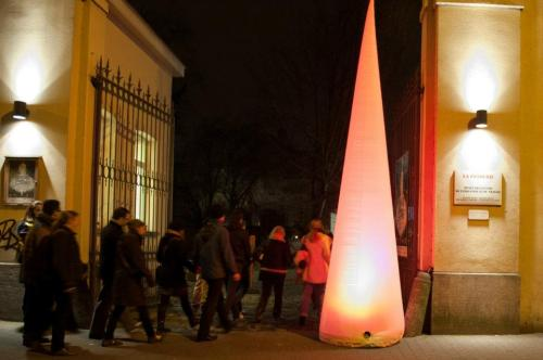 a queue of people entering a gateway at night with a glowing pink sculpture