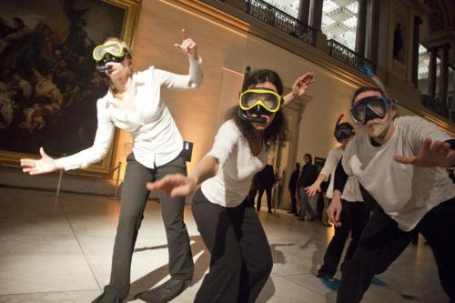Four adults dancing with snorkels in an art gallery