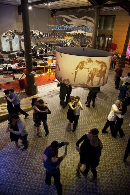 A room of people dancing in pairs surrounded by dinosaurs