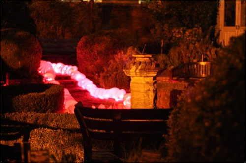 A pink glow-worm installation climbing up stone steps in a garden