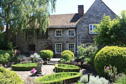A historic building with a carefully manicured garden on a sunny day