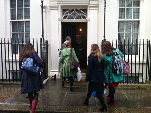 A group of people go through the front door of Number 11 Downing Street