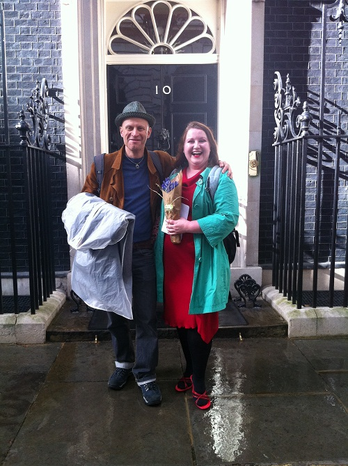 A man and woman grinning outside 10 Downing Street