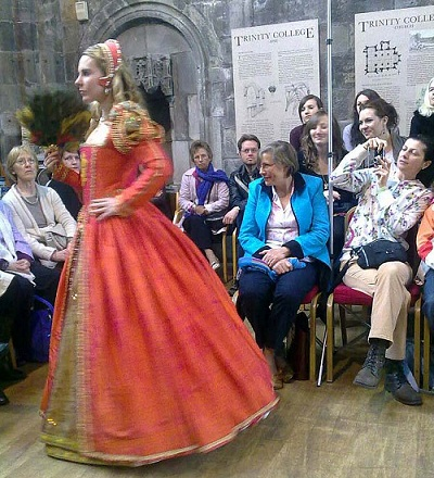 A woman in a Tudor dress on a catwalk in a castle