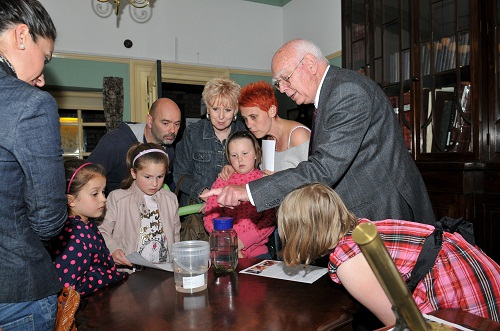 Families stare at a Victorian doctor's jar of leeches