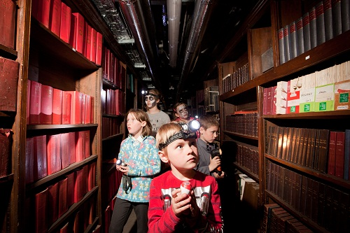 A group of children with torches in a library at night