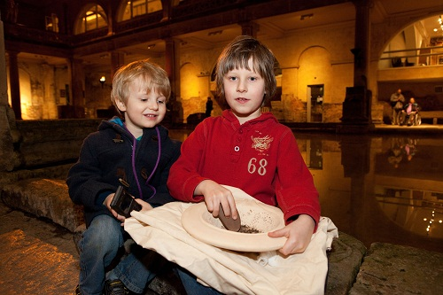 2 boys with a pestle and mortar at a Roman bath