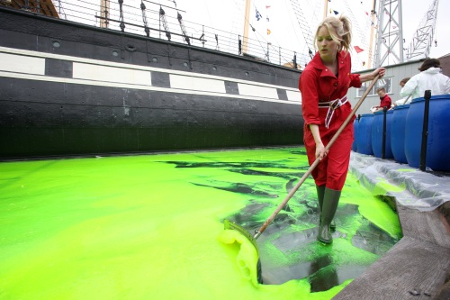 A woman spreading green jelly around a ship