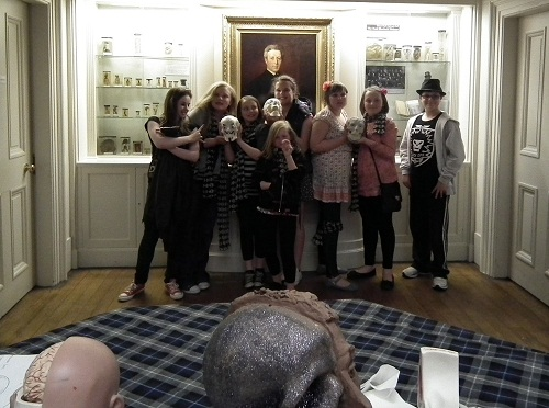 A group of children holding skulls in a museum