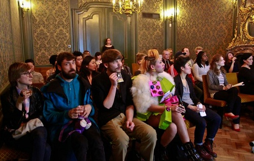 a glamorous audience seated as if to watch a fashion show in a historic room