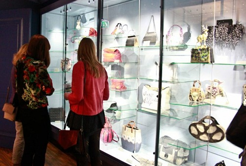 Women looking at a museum display case full of handbags