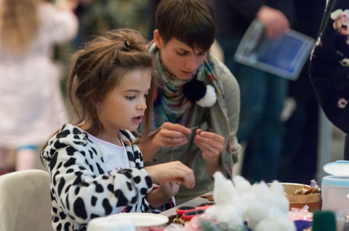 a girl in spotty pyjamas making crafts