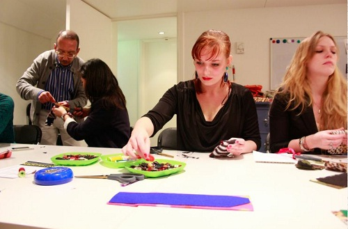 A woman doing a craft project with beads and fabric