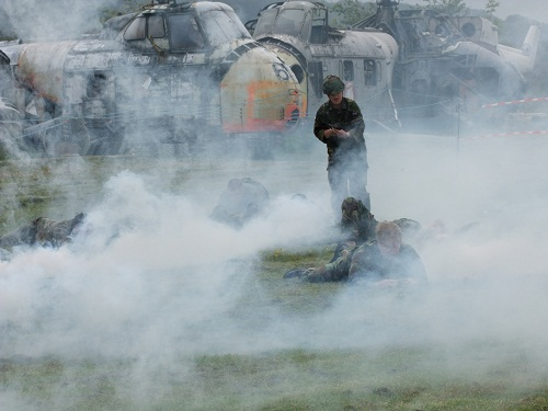soldiers with old helicopters amid clouds of smoke