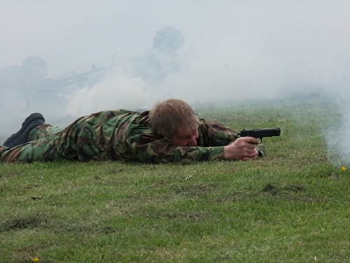 A soldier crawls through a smoky field with a gun