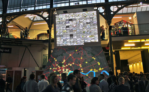 Museum visitors at dusk in front of a digital map installation
