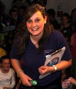 A smiling woman with a torch and clipboard