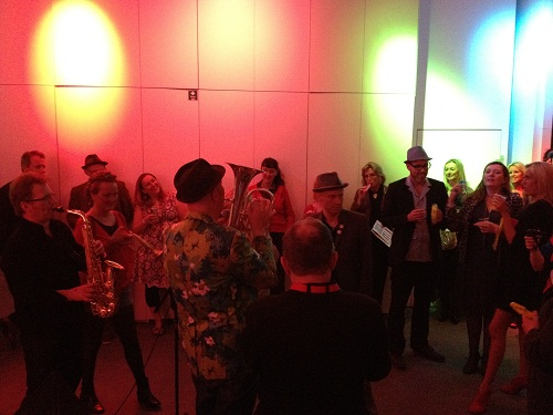 A brass band playing amid a crowd in a dimly lit gallery