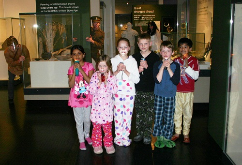 Pyjama-wearing children with torches at a museum after hours