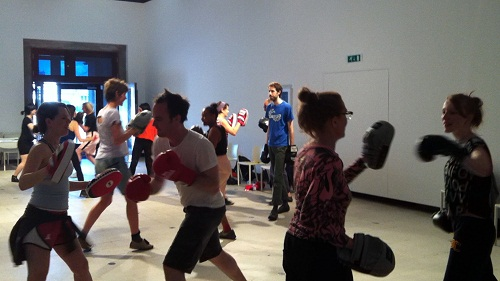 A group of people sparring with boxing gloves and pads in an art gallery