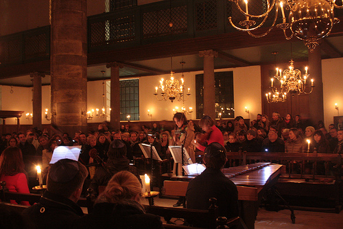 Musicians play to a large audience in a historic synagogue lit only by glowing candles
